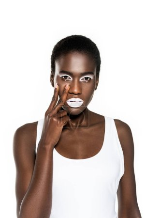 serious young african american woman with white makeup touching face and looking at camera isolated on white