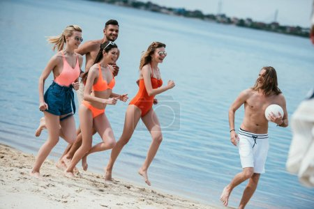 Photo for Happy young friends having fun and running on sandy beach - Royalty Free Image