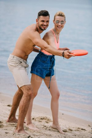 happy young couple playing with flying disc on sandy beach