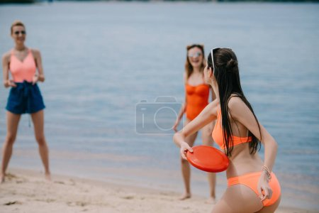 young female friends in swimwear playing with flying disc on sandy beach