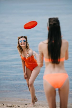 happy girls in swimwear playing with flying disc on sandy beach