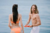 beautiful young couple playing with flying disc on beach
