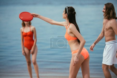 happy young people playing with flying disk on beach