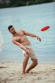 handsome young man throwing flying disk at sandy beach