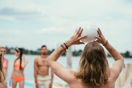 back view of young man playing volleyball with friends on beach