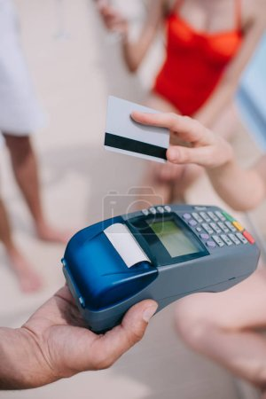 close-up partial view of person paying with credit card on beach