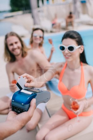 smiling young woman paying with credit card while drinking champagne with friends at poolside