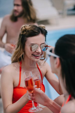 selective focus of young female friends drinking champagne and smiling at pool