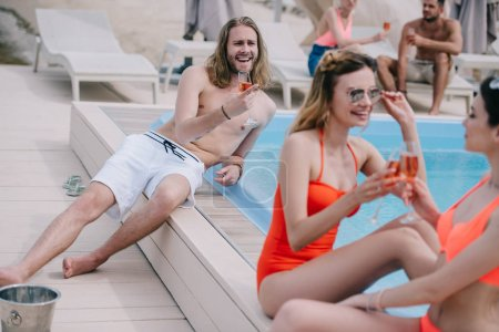 happy young people drinking wine and resting at poolside