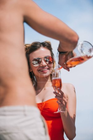 cropped shot of man pouring champagne to smiling young woman in swimsuit