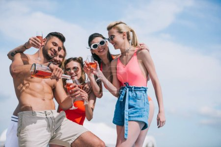 low angle view of happy young friends holding glasses and pouring wine at summer day