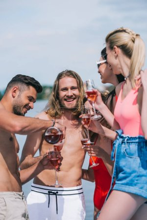 happy young male and female friends holding glases and pouring wine on beach