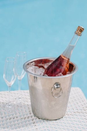 close-up view of bottle of champagne in bucket with ice and two empty glasses at poolside
