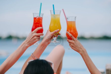 cropped shot of young female friends holding glasses with summer cocktails at beach