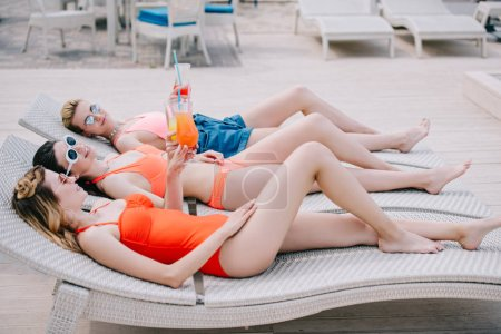 attractive female friends in swimwear and sunglasses resting with cocktails on chaise lounges