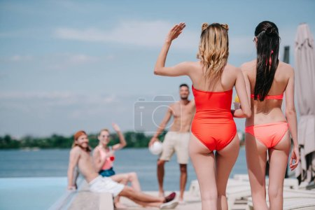 back view of girls in swimwear walking on beach and waving hand to friends at poolside