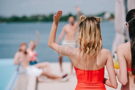 Photo for Back view of young woman waving hand to friends on beach - Royalty Free Image