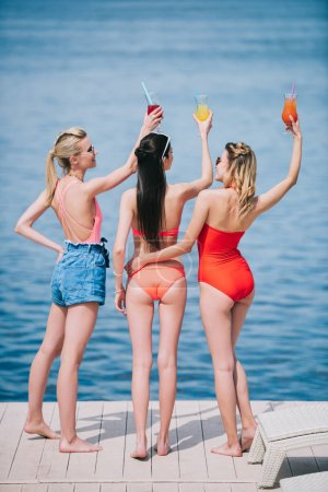 back view of three young women in swimwear holding glasses with summer cocktails on beach