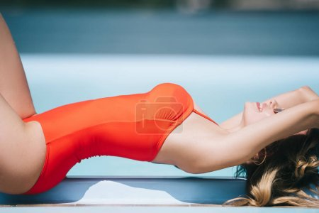 smiling young woman in swimsuit resting near pool