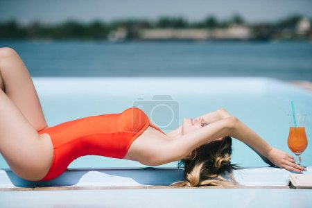 side view of beautiful young woman in swimsuit resting with summer cocktail near pool