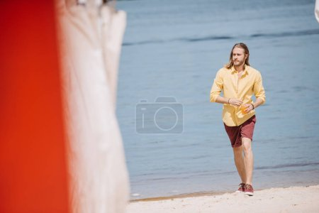 selective focus of handsome young man holding glass with cocktail and looking away while walking at beach