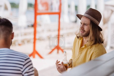 young man holding beer bottle and looking at friend sitting at beach bar