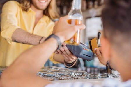 cropped shot of young man holding beer bottle and paying with credit card at beach bar