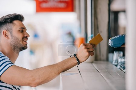 side view of smiling young man paying with credit card at beach bar