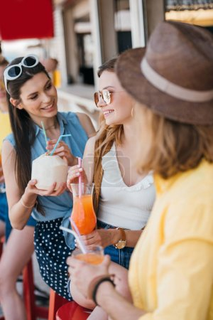selective focus of smiling young friends drinking cocktails at beach bar