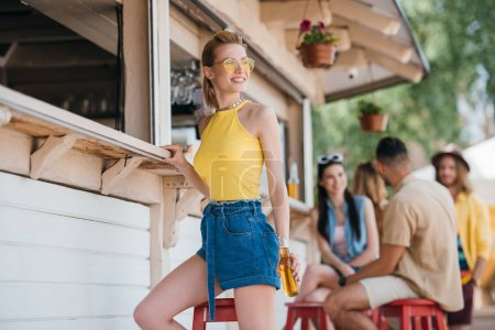 smiling young woman holding beer bottle while friends sitting behind at beach bar
