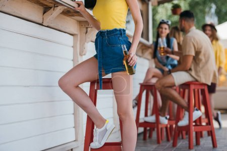 cropped shot of girl holding beer bottle while friends sitting behind at beach bar