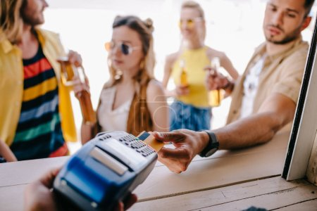 cropped shot of young man paying with credit card and payment terminal at beach bar
