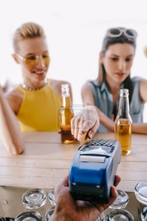 selective focus of girls drinking beer and paying with credit card on terminal in beach bar