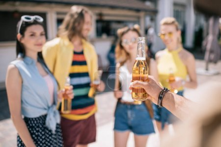 selective focus of young friends drinking beer on beach