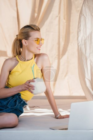 beautiful smiling young woman in sunglasses holding summer coconut cocktail and looking away