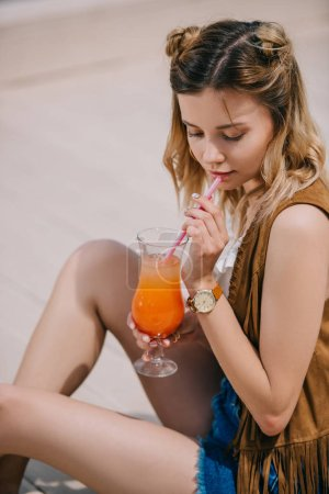 beautiful young woman drinking summer cocktail outdoors