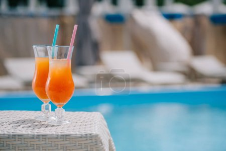 close-up view of glasses with summer cocktails and drinking straws at poolside