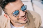 close-up portrait of handsome young man in sunglasses smiling outdoors