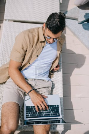 high angle view of young man in sunglasses lying on chaise longue and using laptop
