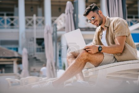 smiling young man in sunglasses using laptop while resting on chaise longue