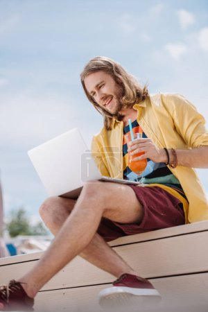 smiling young man holding cocktail and using laptop at beach