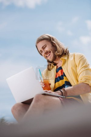 low angle view of smiling young man holding cocktail and using laptop at beach