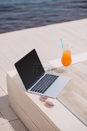 laptop with blank screen, sunglasses and glass with cocktail at beach