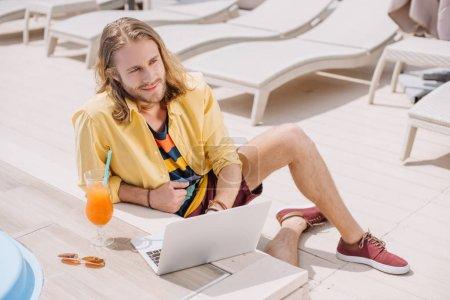 Photo pour Vue de la forte inclinaison du souriant jeune homme utilisant l'ordinateur portable tout en se reposant avec cocktail au bord de la piscine - image libre de droit