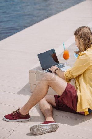 high angle view of young man using laptop with blank screen at beach