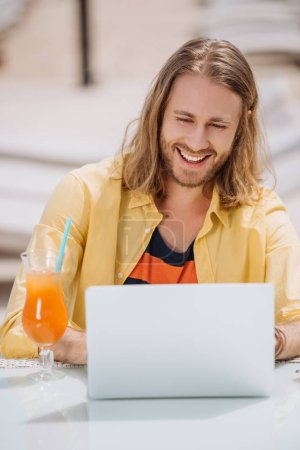 smiling young man using laptop while sitting outdoors at sunny day