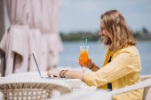 side view of smiling young man holding cocktail and using laptop at beach
