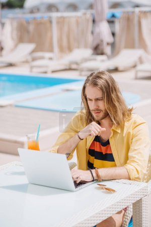 handsome young man drinking cocktail while sitting near pool