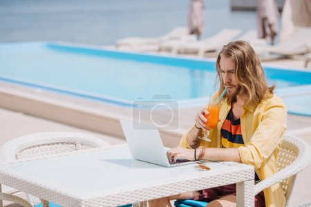 handsome young man using laptop and drinking cocktail near pool