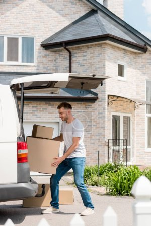 young smiling man moving boxes from car into new house